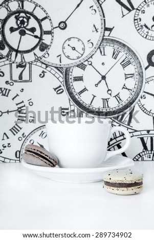 Time for Tea, tea cup with French macaron cookies and vintage clock background