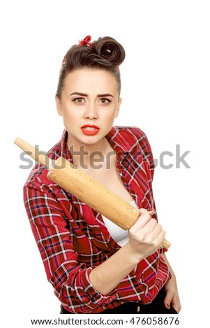 Time for the payback. Shot of a stunning hot pinup girl wearing a bandana and a plaid shirt pointing a rolling pin to the camera looking angry isolated on white