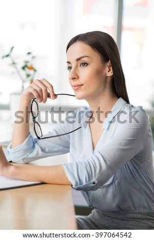 Time for thoughts. Pleasant charming woman sitting at the table and holding her glasses while being involved in thinking - stock photo