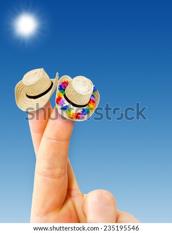 Time for  travel - two fingers with straw hat - stock photo