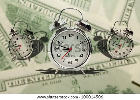 Time is money. Alarm clock on money background