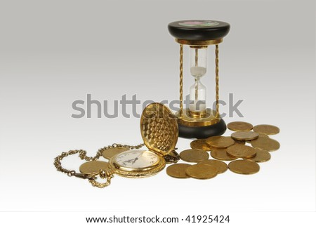 Time is money .An antique pocket watch with and hourglass surrounded by coins - stock photo
