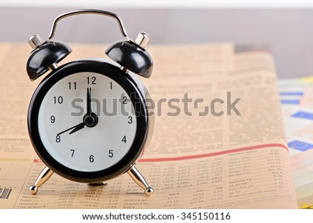 Time is money. Business concept. Alarm clock on the financial pink newspaper - stock photo