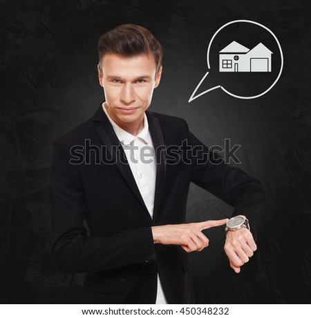 Time is money. Businessman point at his watch showing hand clock, real estate buying concept. Man in suit at black background, thinking cloud with house. Rent, lease, sell property. - stock photo