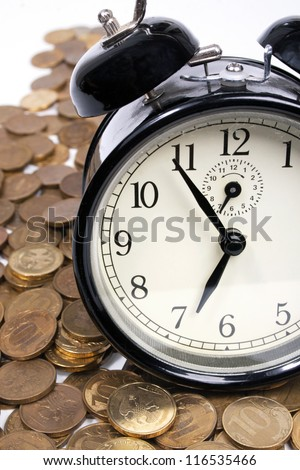 Time is money concept.  Coins and an old alarm clock - stock photo