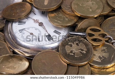 Time is money concept.  Coins and an old pocket-watch.