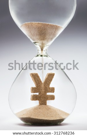 Time is money concept with hourglass falling sand taking the shape of a yen/yuan - stock photo
