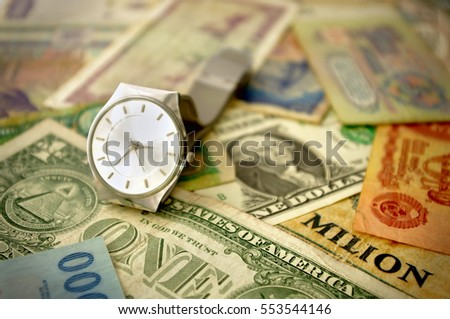 time is money concept with watch and old banknotes