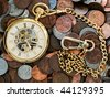 Time is money conceptual closeup of gold pocket watch with a background of United States coins. Pennies,nickles, dimes - stock photo