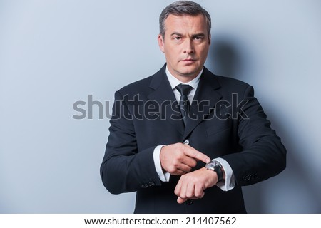Time is money. Confident mature man in formalwear pointing his watch and looking at camera while standing against grey background - stock photo