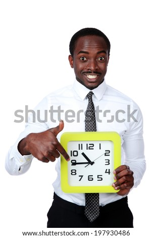 Time is money! Handsome african man holding a clock and showing on it - stock photo