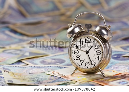 Time is money. Old alarm clock on large amount of banknotes - very old and new romanian banknotes and euros. - stock photo