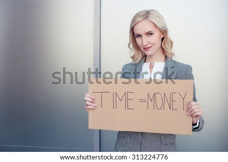 Time is money. Successful woman in formalwear is standing and holding a billboard. She is looking forward confidently and smiling. Copy space in left side - stock photo