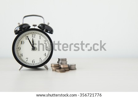 Time is money, table clock with coins on white background