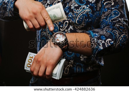 Time is money. The concept of time and money. A man holding a lot of money and shows up on time. - stock photo