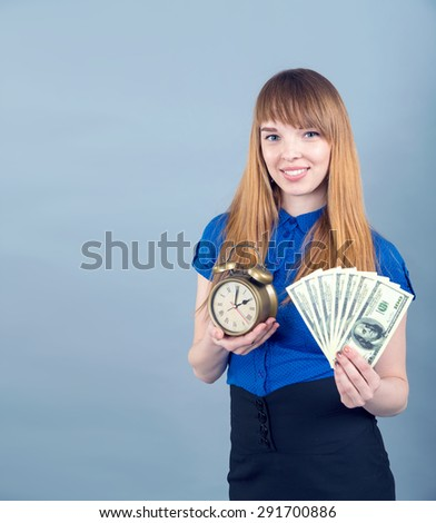 Time is money. Young woman with dollars in her hands. Happy young woman hold money one hundred dollar bills in hand on the blue wall background. - stock photo