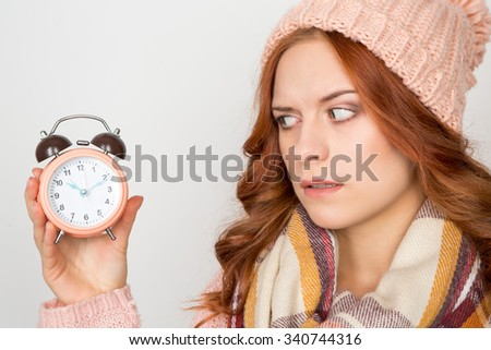 Time is running too fast for her. Closeup portrait of a young Caucasian female wearing winter clothes holding clock in her hand and looking at it pretentiously  - stock photo