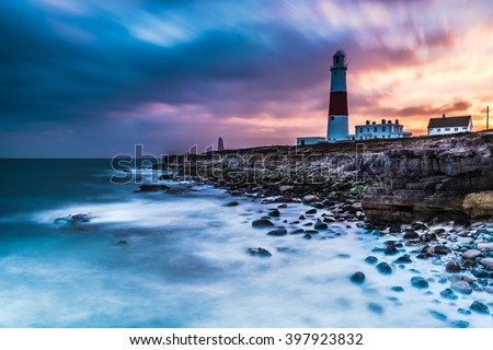 Time lapse of dramatic sunset and Portland Bill lighthouse, on rocky shore at Portland, Dorset, UK.