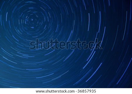 Time-lapse photo of stars rotating in a night sky - stock photo