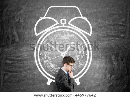 Time management concept with thoughtful businessman against chalkboard wall with alarm clock sketch - stock photo