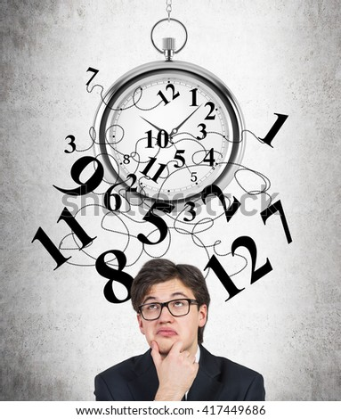 Time management with broken clock and thinking businessman with funny expression on concrete background - stock photo