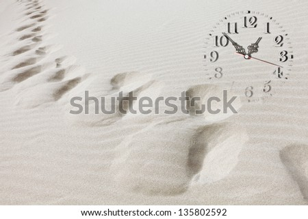 Time passing concept - clock image, sand dune and human foot traces. Time passing concept - stock photo