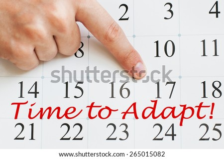 Time to adapt written on a calendar page with a finger pointing on it - stock photo