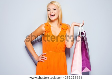 Time to buy new dresses. Beautiful young woman in pretty dress looking at camera and holding shopping bags standing against grey background   - stock photo