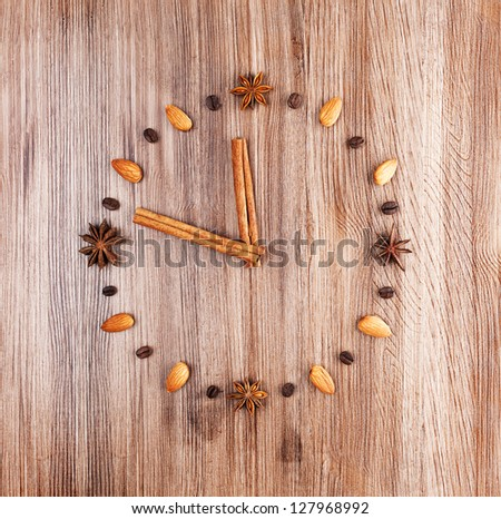 Time to cook. Clock face on a wooden background of almonds and coffee beans with arrow of cinnamon sticks. - stock photo