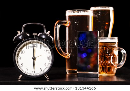 time to drink beer. glasses of fresh lager beer with clock and mobile phone - stock photo