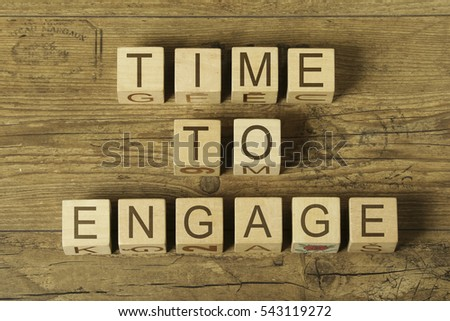 time to engage text on cubes on wooden background