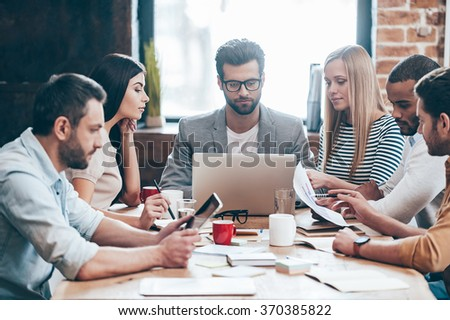 Time to familiarize new business plan! Group of six young people reading and looking threw charts while sitting at the table in office - stock photo