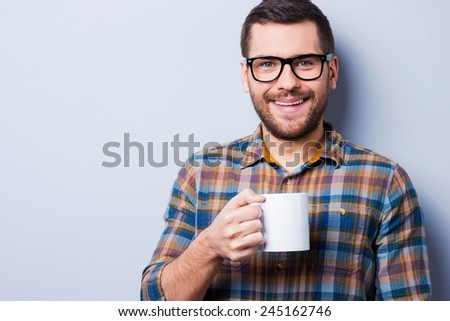 Time to have a brake. Handsome young man drinking coffee and looking at camera while standing against grey background - stock photo