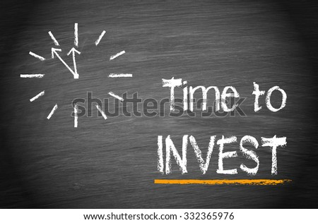 Time to invest - clock with text on blackboard background - stock photo