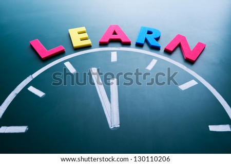 Time to learn concept, color word and clock on blackboard - stock photo