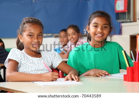 Time to learn two cheerful school girls in class - stock photo