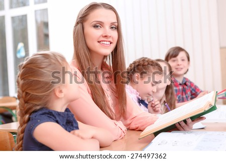 Time to read. Young smiling teacher sitting at desk near pupils, holding book and reading to them - stock photo