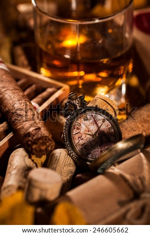 Time to relax! A complete set of male pleasures: a glass of whiskey, havana cigars in open humidor box and pocket watches in memory of a trip to Paris - stock photo