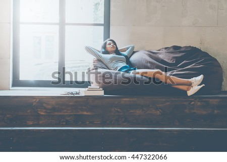 Time to relax. Beautiful young mixed race woman holding hands behind head and keeping eyes closed while lying on the comfortable couch and near the large window  - stock photo