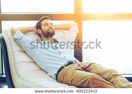 Time to relax. Handsome young man holding hands behind head while sleeping on the couch - stock photo