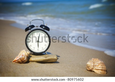 Time to relax! The sea is calling!  The alarm and seashells on the shore of the warm sea - stock photo