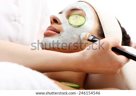 Time to relax, the woman at day spa salon. Cosmetic procedure woman's face in the mask mitigating and cucumber slices on eyes  - stock photo