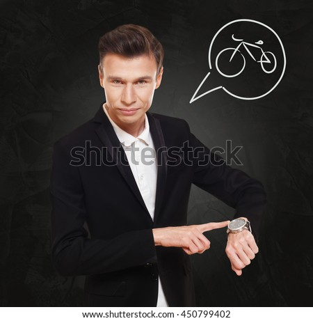 Time to ride a bicycle. Businessman point at his hand watch showing clock. Man in suit at black background, thinking cloud with bike symbol. Travel ecological transport, cycling sport leisure concept - stock photo