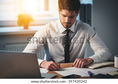 Time to sign some contracts. Pensive young handsome man signing documents while sitting at his working place - stock photo