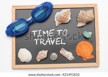Time to Travel text on chalk board with swimming goggle and shell - vacation and business concept - stock photo