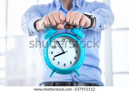 Time to work! Businessman holding a big clock in his hands. Close-up view of the big clock in the hands of a businessman. - stock photo