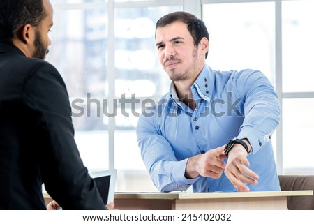 Time work. Serious businessman sitting at the negotiating table in the office and indicates your watch. Business people dressed in formal wear - stock photo