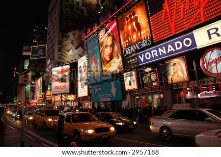 Times Square at night with traffic and yellow cabs