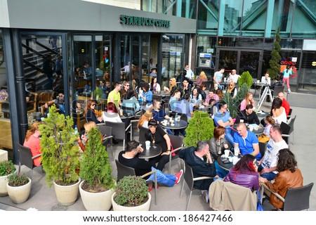 TIMISOARA, ROMANIA - APRIL 6, 2014: People at the Starbucks coffeehouse in Iulius Mall, Timisoara, Romania - stock photo