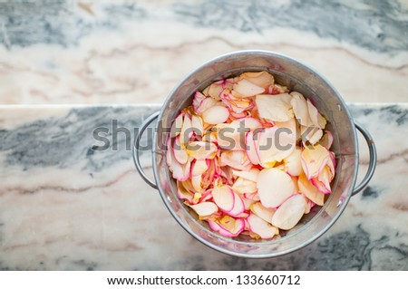 tin bucket filled with rose petals to throw at the wedding ceremony, top view shallow depth of field - stock photo